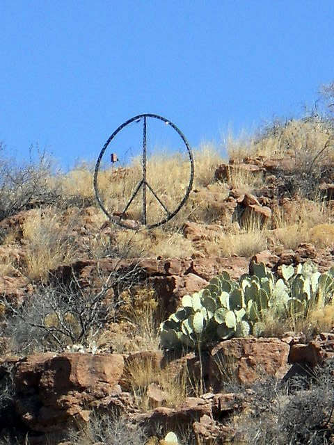 Photo of peace symbol on rocky hillside